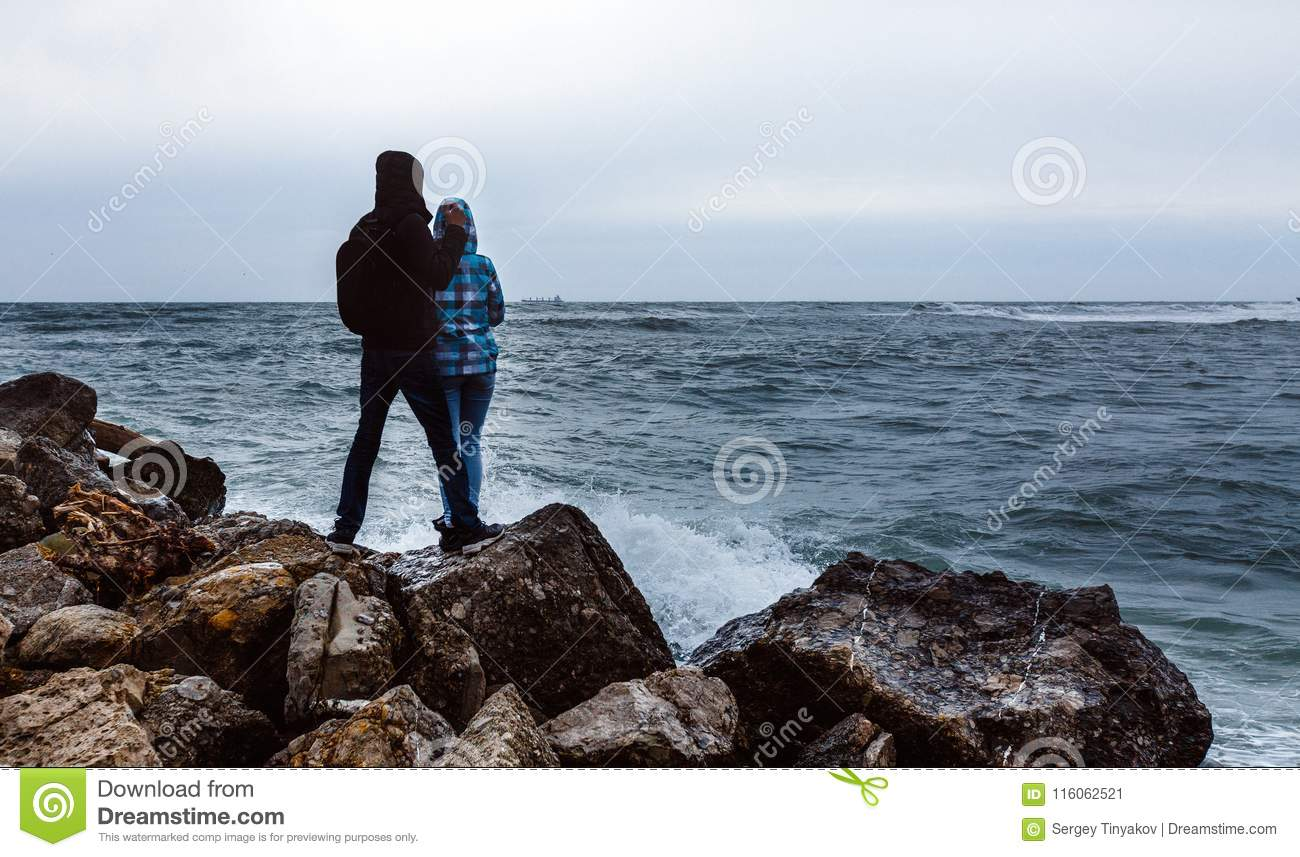 Happy Young Couple Standing Against A Stone Beach And Enjoy View
