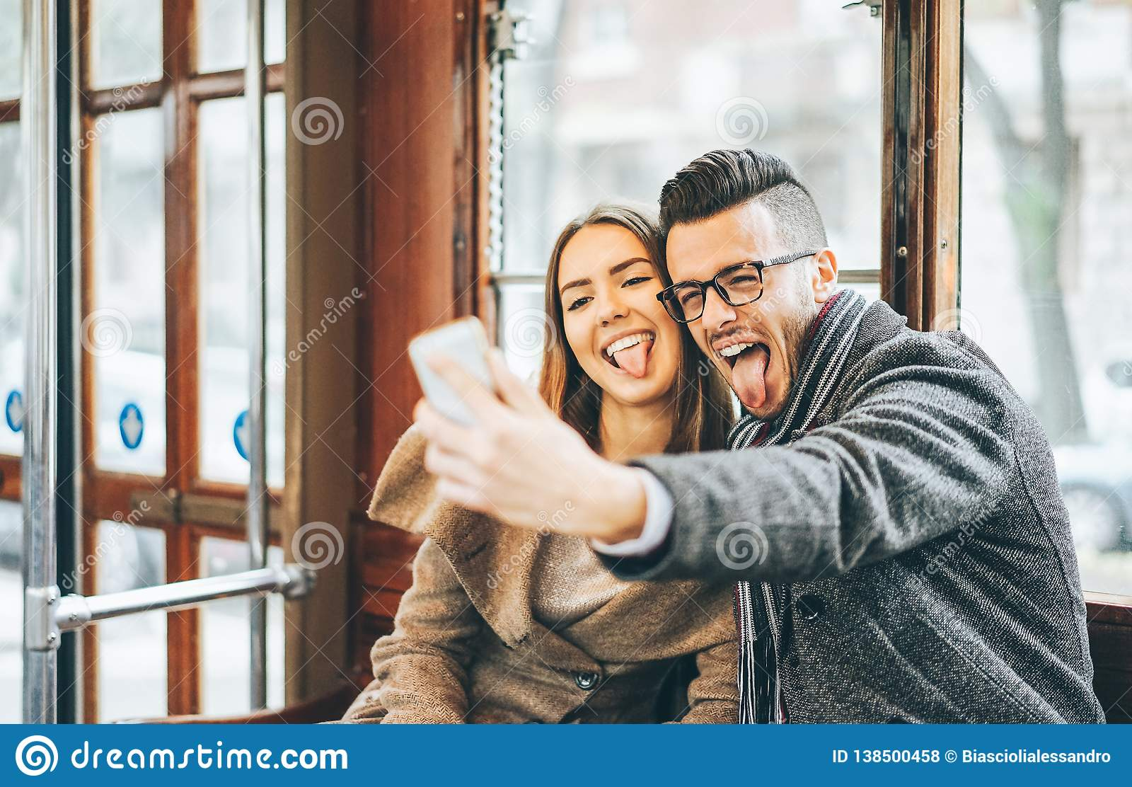 Happy young couple taking photos using mobile smart phone camera inside bus - Travel lovers making a self portrait to post