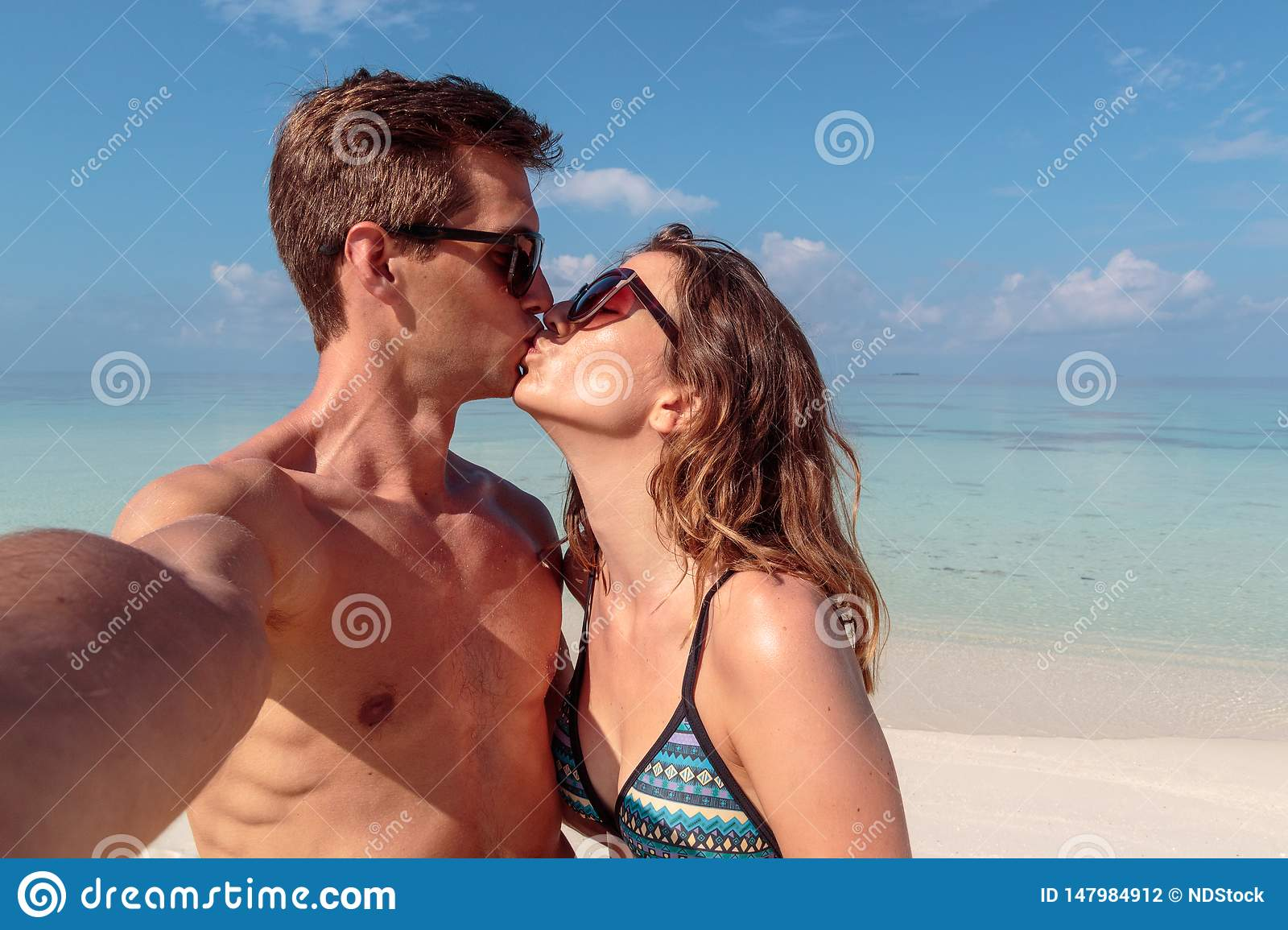 Happy young couple taking a selfie, clear blue water as background. Girl kissing his boyfriend
