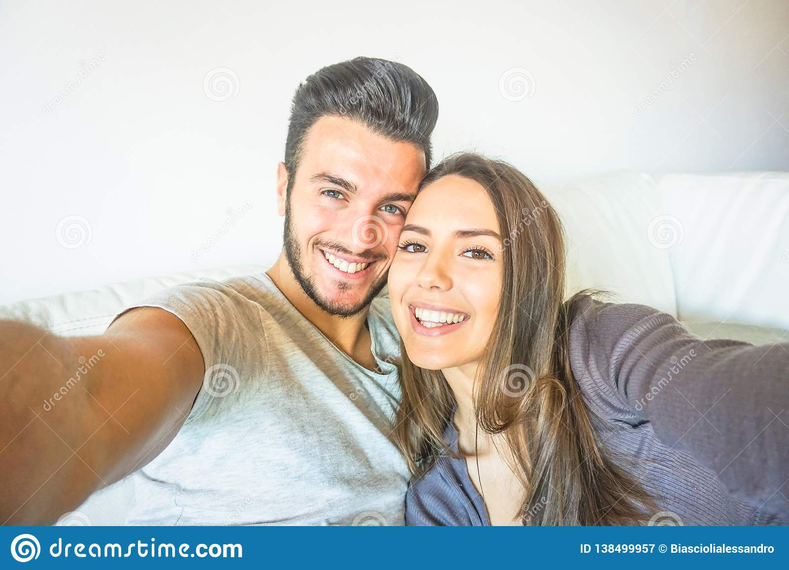 Happy young couple taking a selfie with mobile smart phone camera in the living room embracing on sofa at home