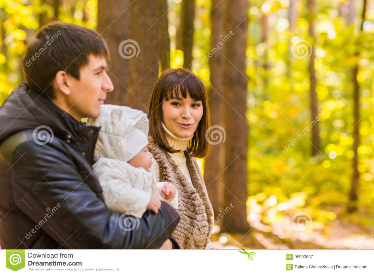 Happy young family in the autumn park outdoors on a sunny day. Mother, father and their little baby boy are walking in