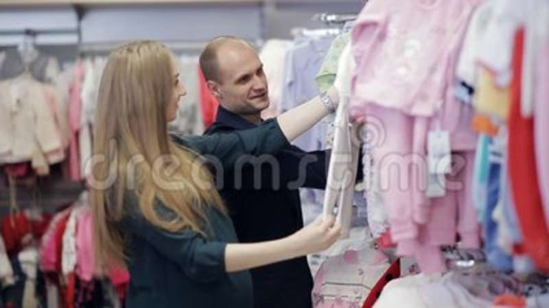 d7058bfdc Young Happy Pregnant Woman Choosing Newborn Clothes At The Baby Shop ...