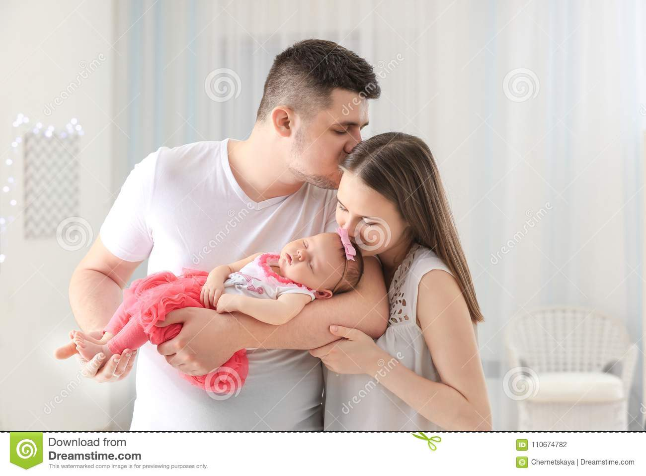Happy young family with cute sleeping newborn baby