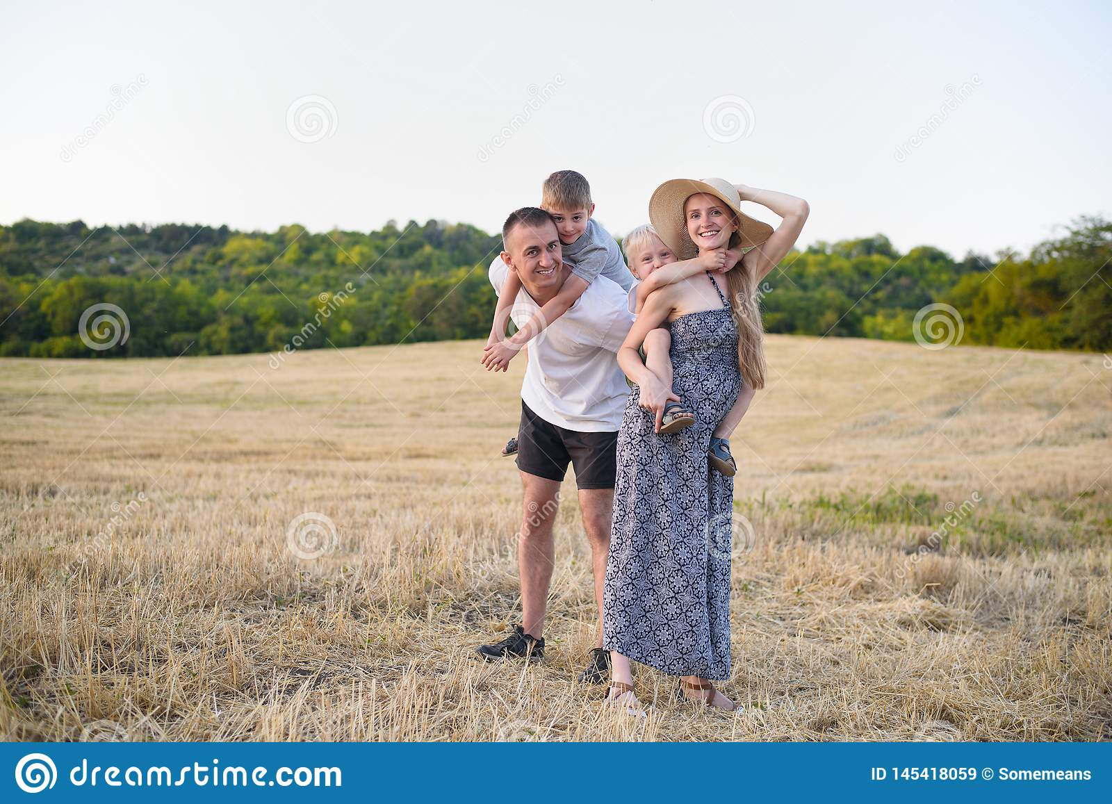 Happy young family. A father, a pregnant mother, and two little sons on their backs. Beveled wheat field on the background. Sunset