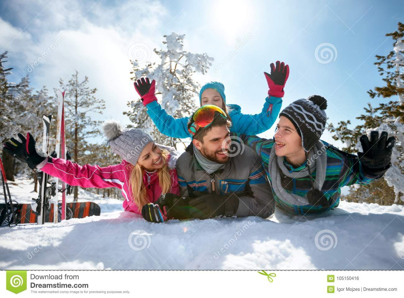 Young family having fun on fresh snow on winter vacation
