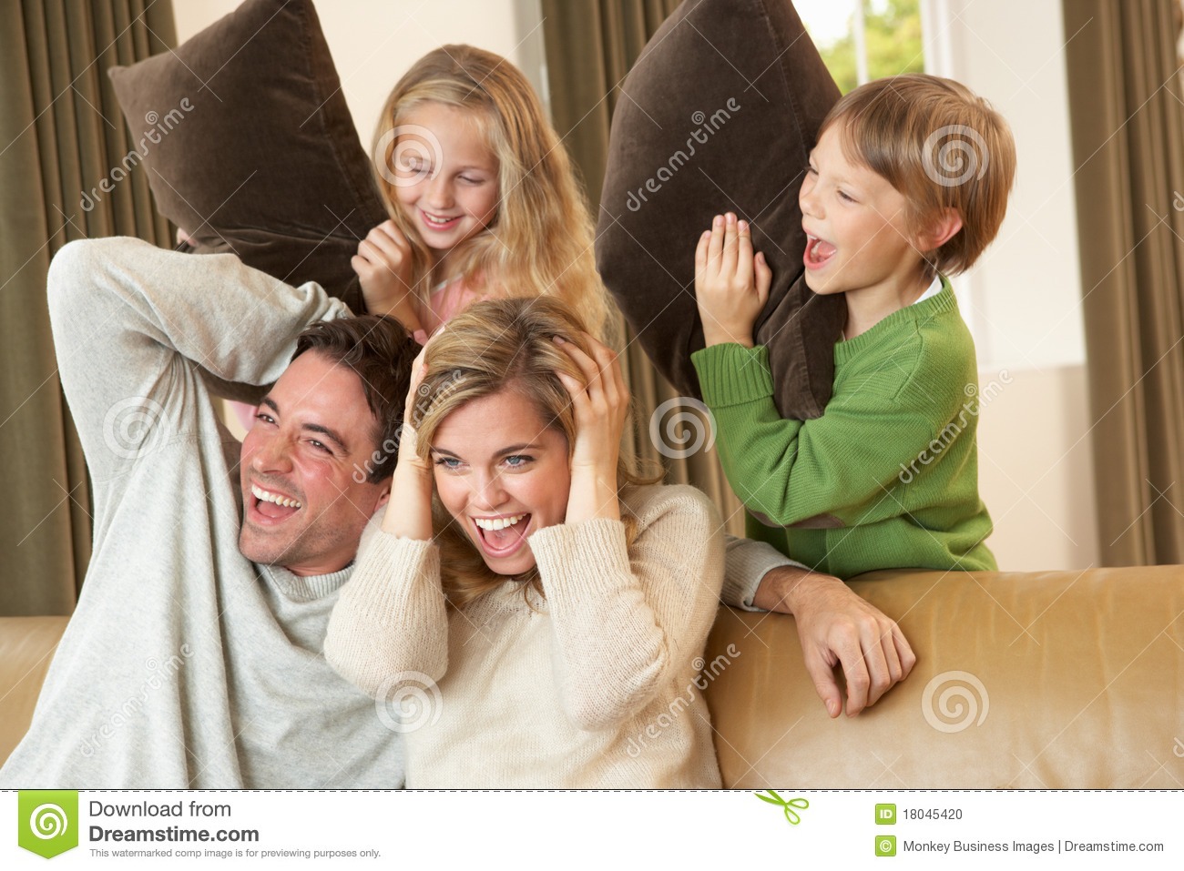 Happy young family having fun with pillows on sofa