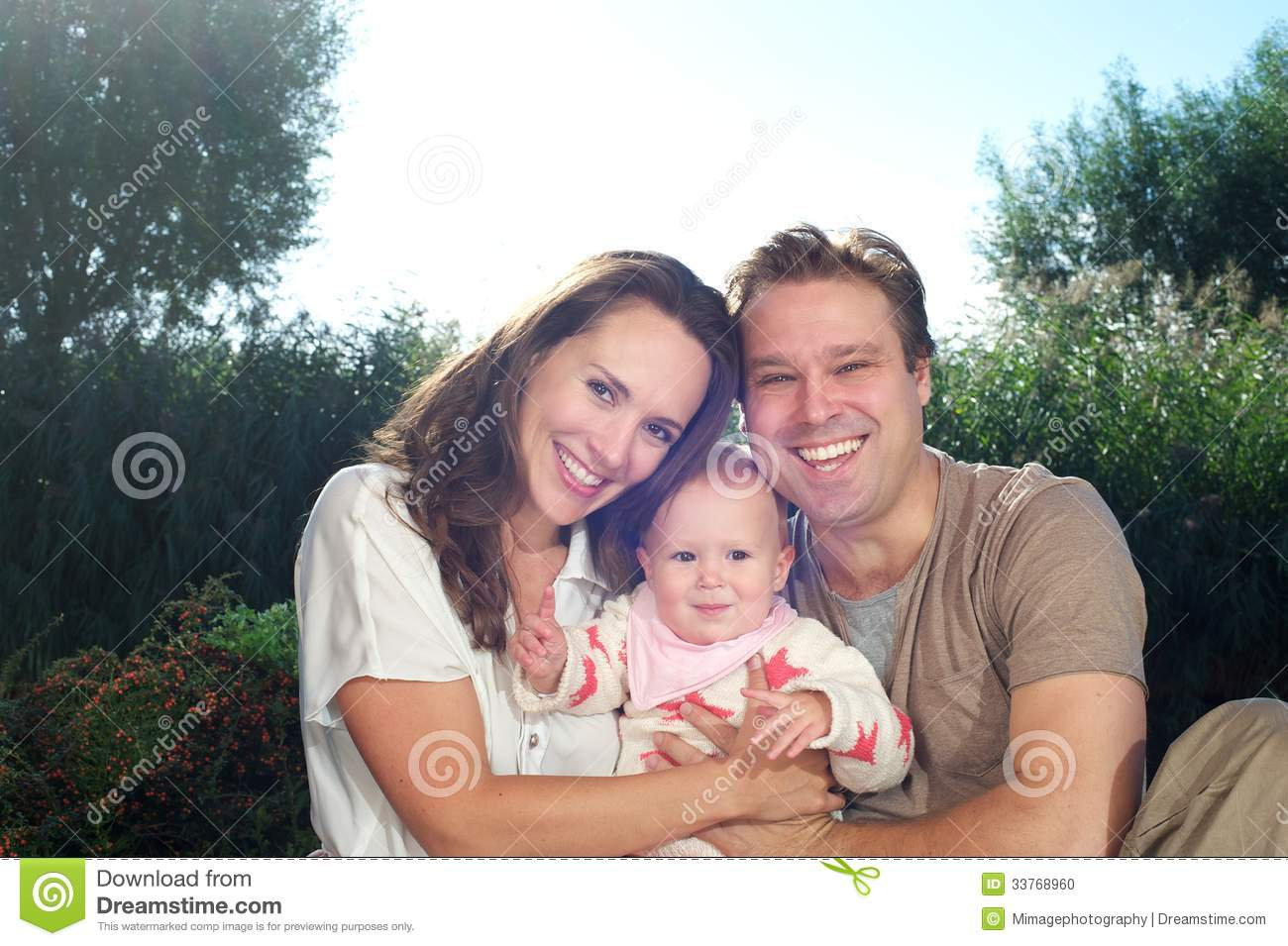 Happy young family holding cute baby outdoors