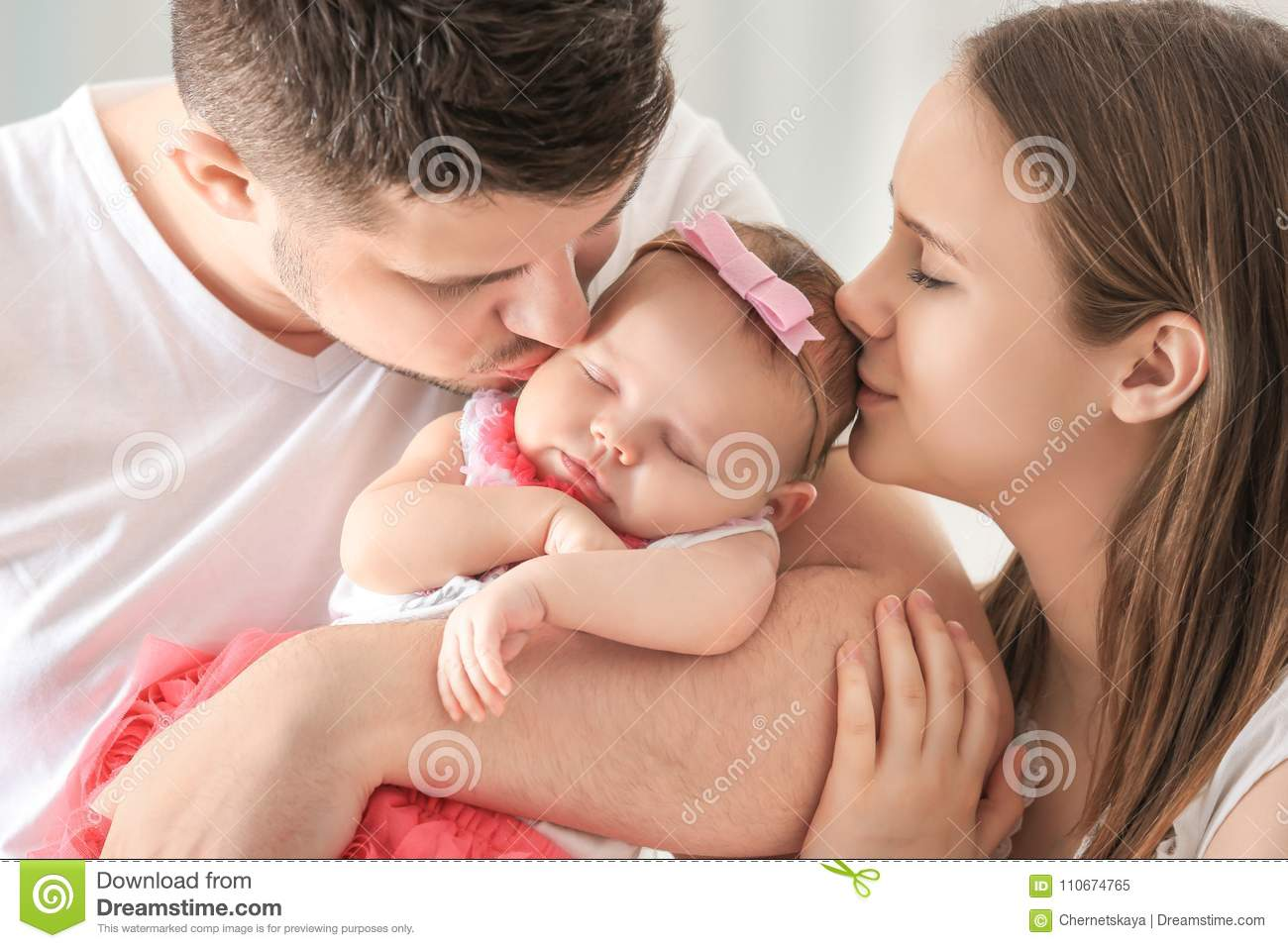 Happy young family holding cute sleeping newborn baby