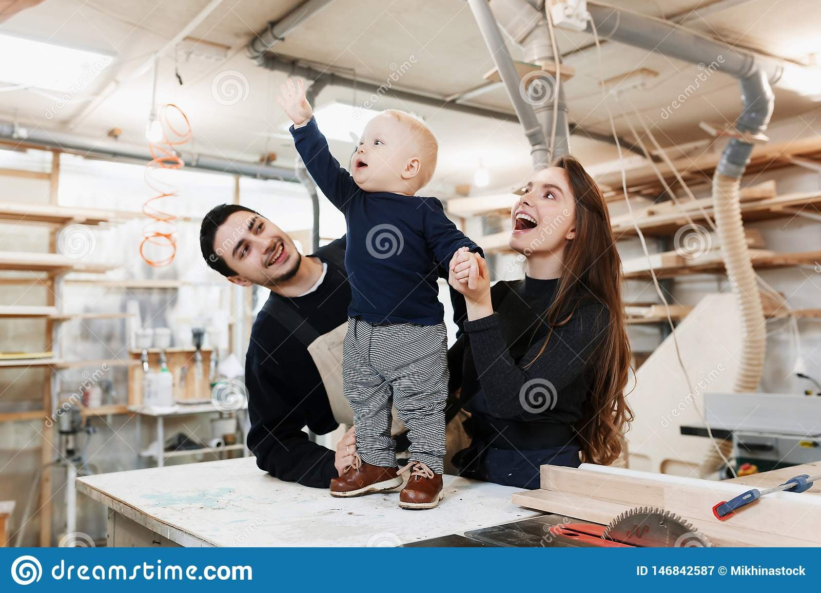 Happy young family with the little son in the carpenter workshop