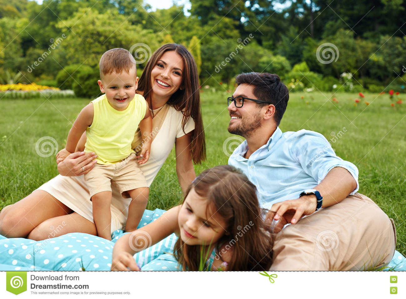 e044c130b06 Happy Young Family In Park. Parents And Kids Having Fun