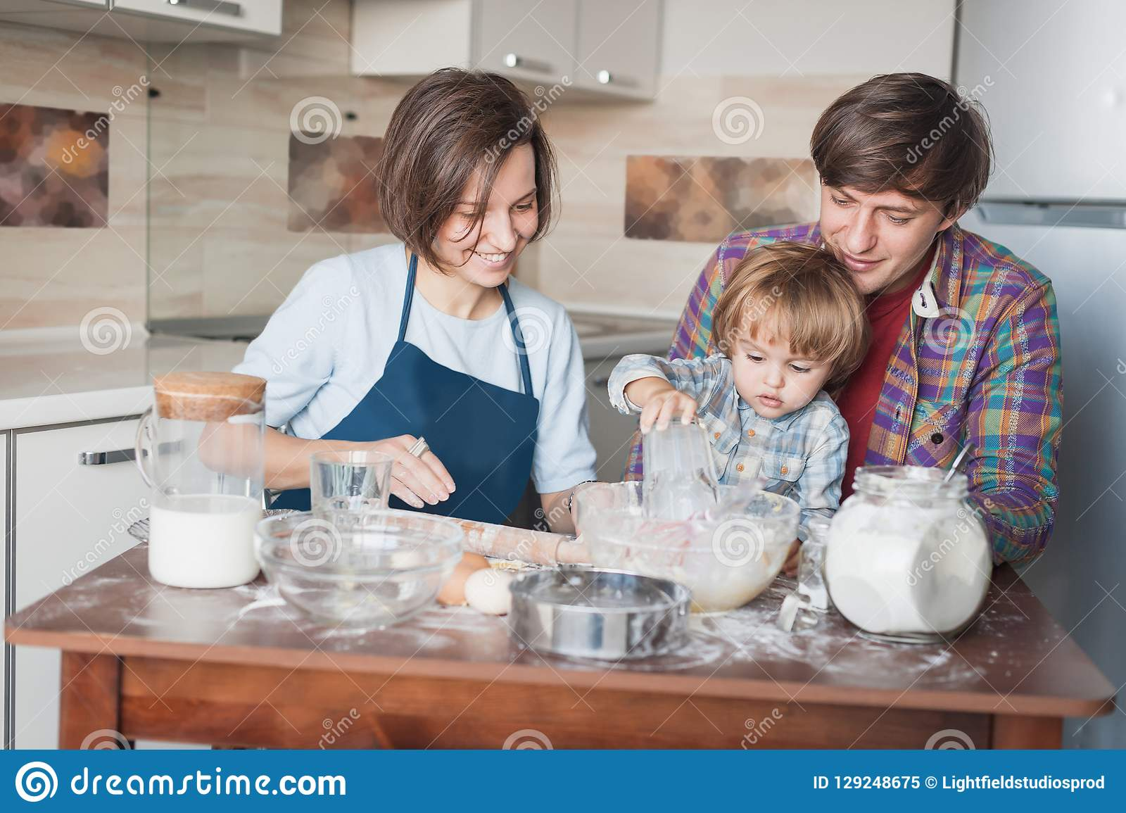 happy young family preparing dough for cookies