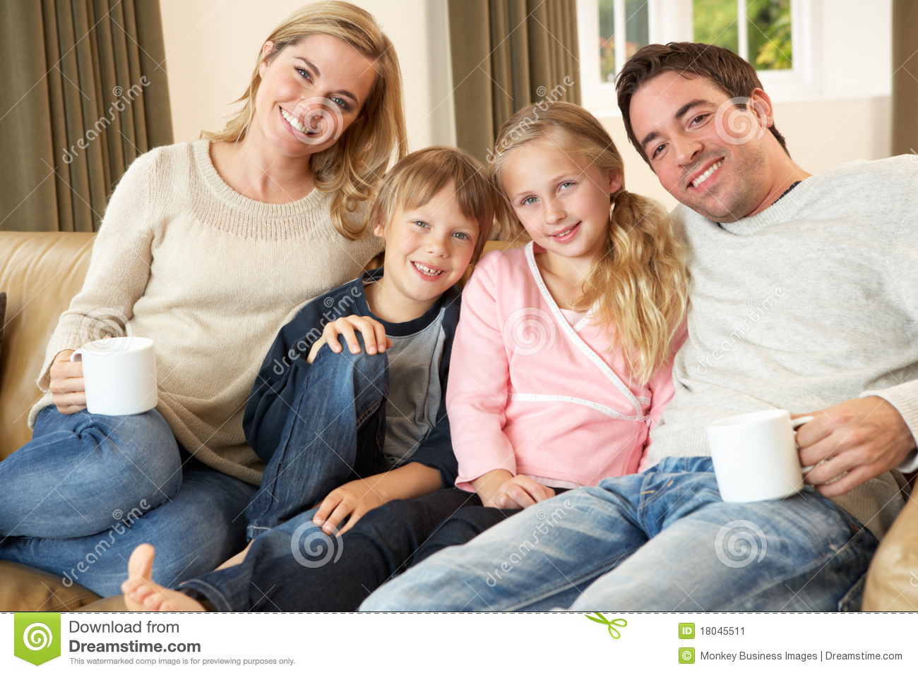Happy young family sitting on sofa holding cups