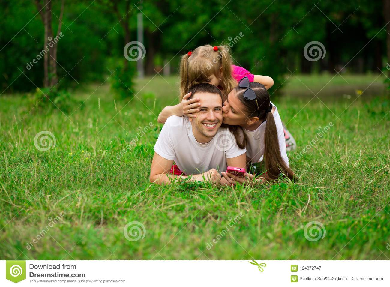 Happy young family spending time outdoor on summer day. Happiness and harmony in family life