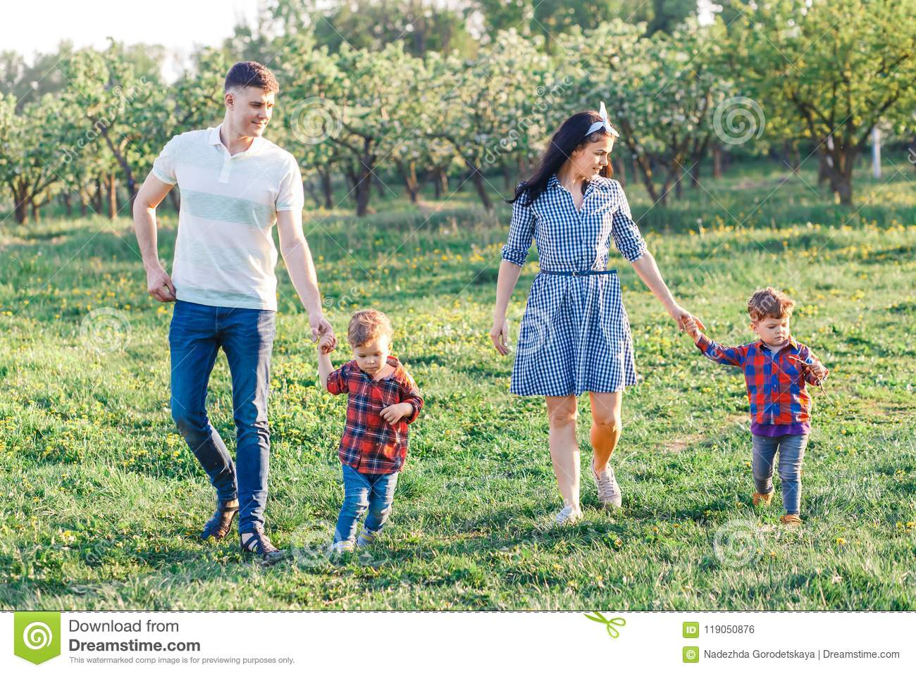 Happy young family spending time together outside in green nature. Parents playing with twins outside.