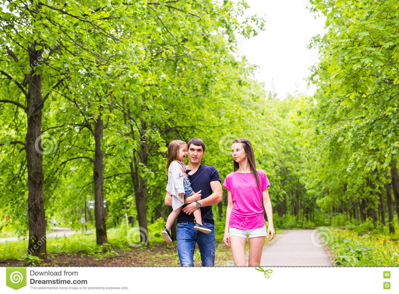 Happy young family walking in green nature.
