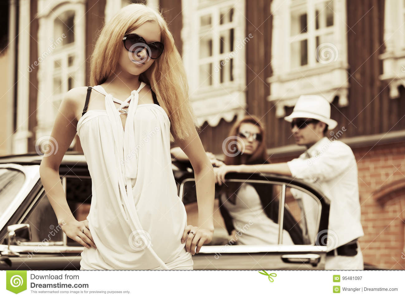 Happy young fashion blond woman in white dress next to vintage car