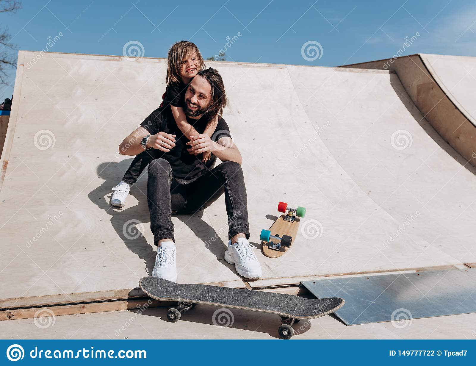 Happy young father and his son dressed in the stylish casual clothes are sitting in an embrace together on the slide