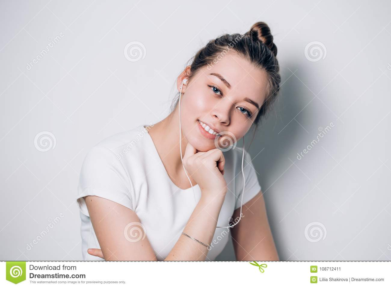 Happy young fit woman using cell phone while listening to music on smartphone