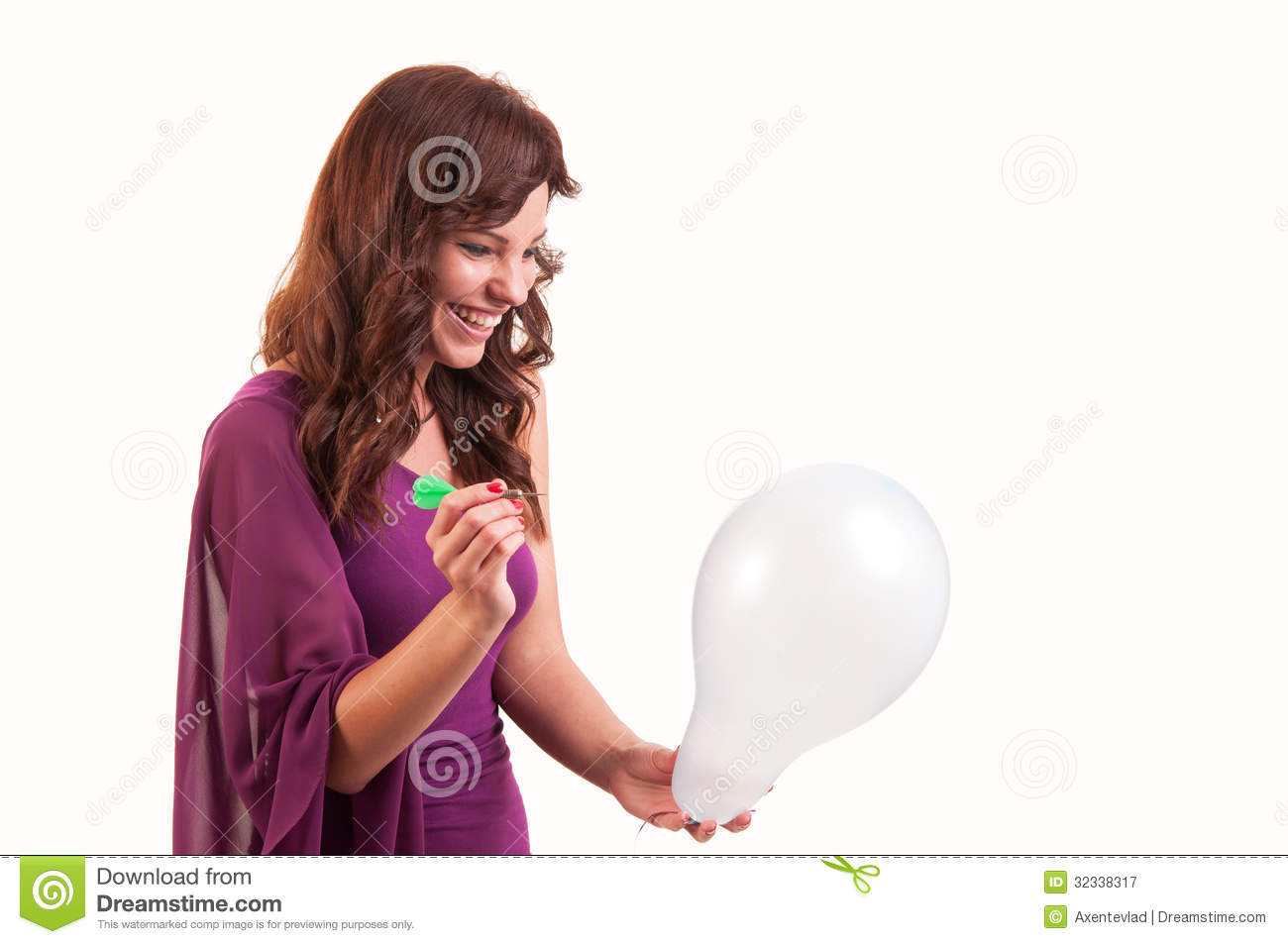 Happy young girl is going to break a balloon with a dart