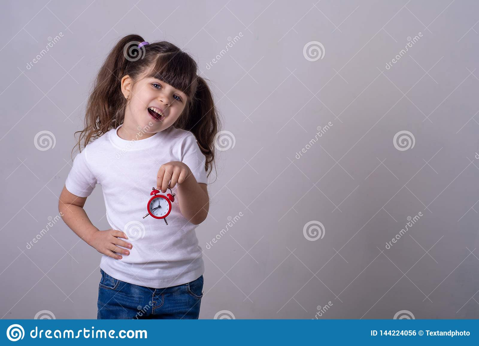 Happy child holding red clock on grey background. Kid with alarm clock