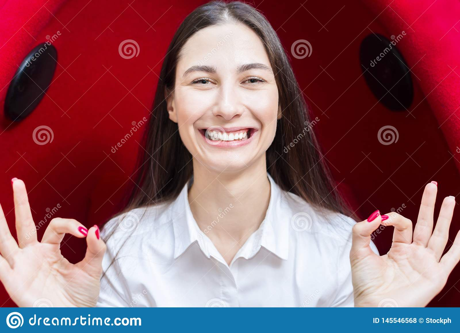 Happy young girl smiling. woman shows gesture everything is fine. red background.
