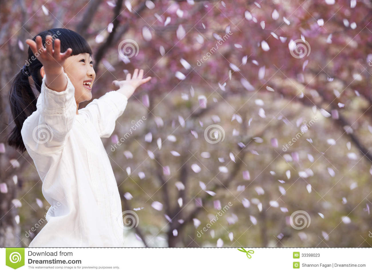 Happy Young Girl Throwing Cherry Blossom Petals In The Air