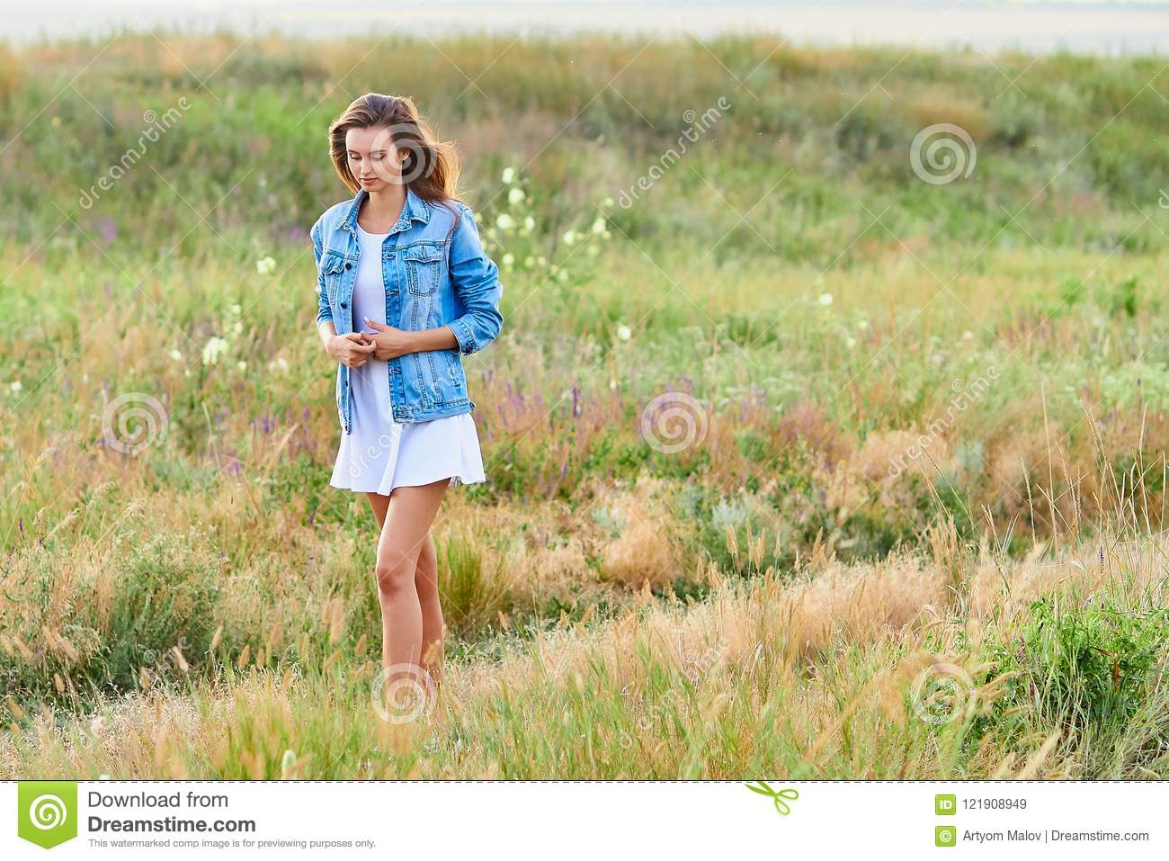 52a12fb876 Happy smiling young girl wearing blue jeans jacket and white dress is  standing in the field