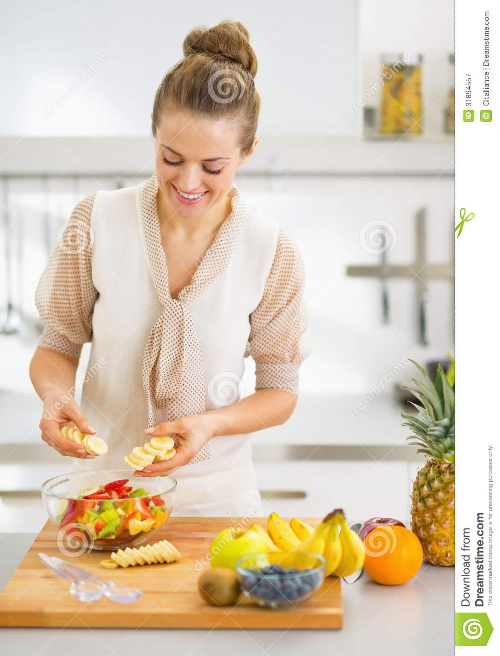 Happy young housewife making fruits salad stock image for Modern housewife