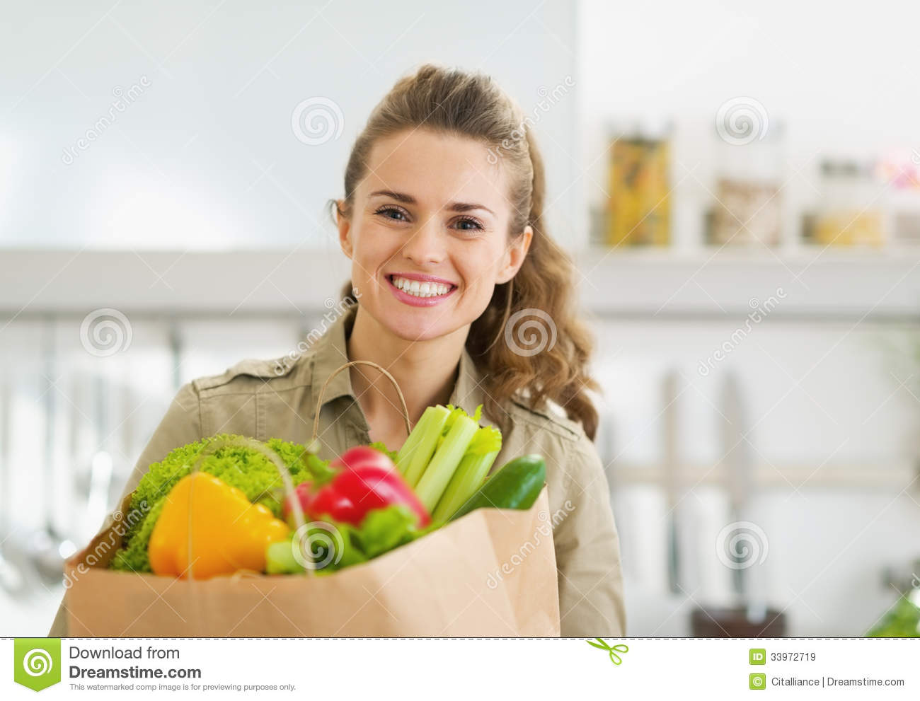 Happy young housewife with shopping bag full of vegetables for Modern housewife