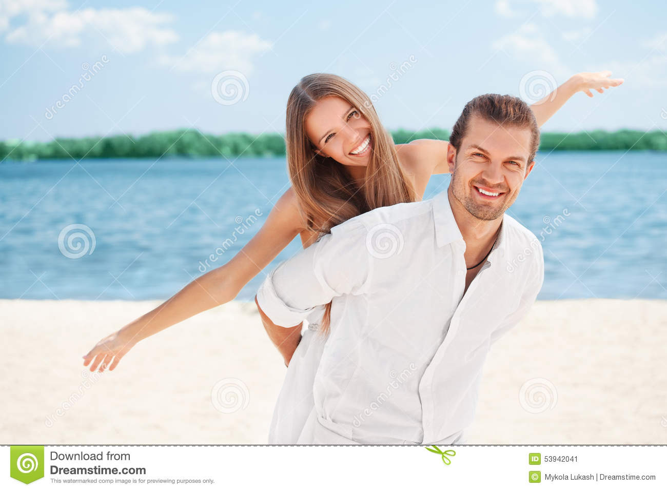 Happy young joyful couple having beach fun piggybacking laughing together during summer holidays vacation on the beach. Beautiful