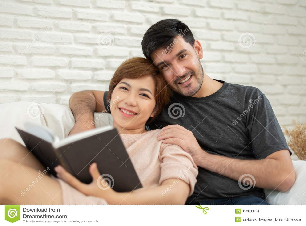 Happy young loving couple reading a book.
