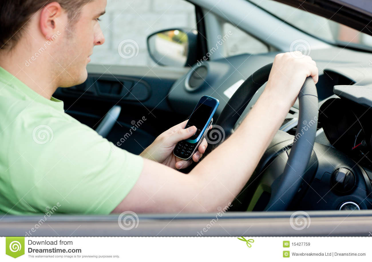 Happy young male driver sitting in a car