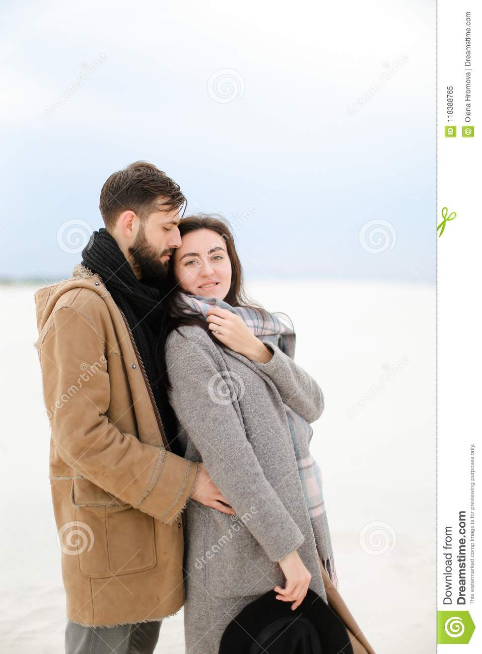Happy young man with beard hugging female person wearing grey coat and scarf, white winter monophonic background.