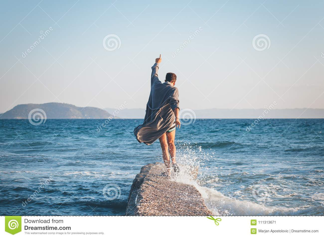 Happy young man dancing on the dock