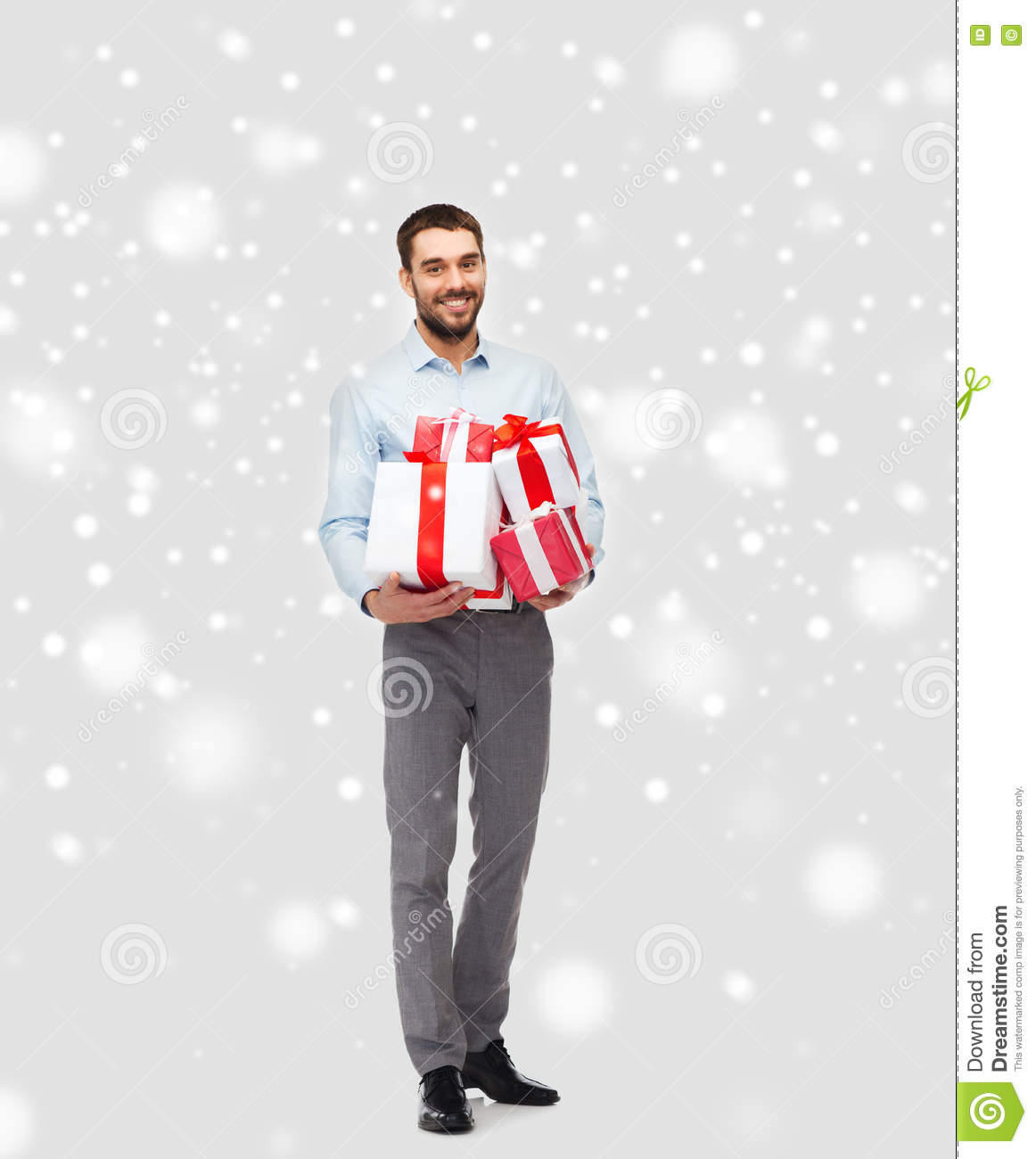 happy young man holding christmas gifts over snow
