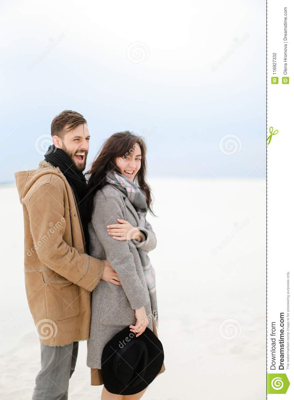 Happy young man hugging female person wearing grey coat and scarf, white winter monophonic background.