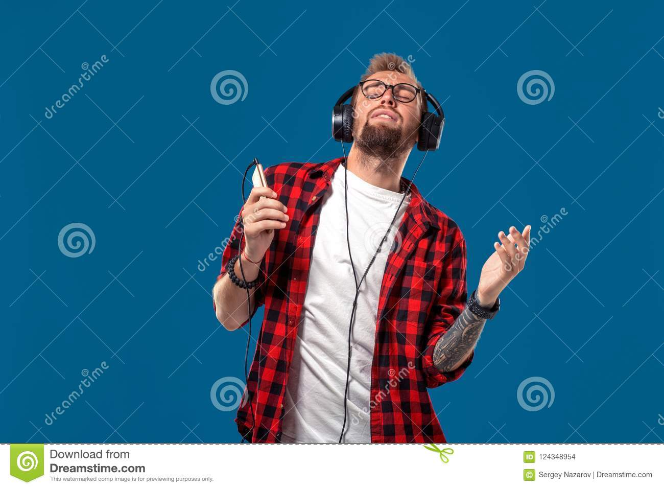 d5221a0f Happy young man listening to music with headphones. Handsome smiling guy in  checkered shirt with