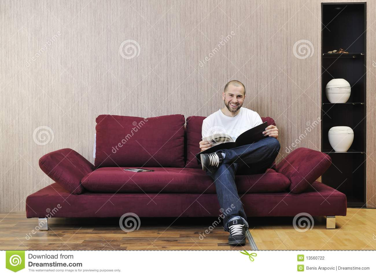 Happy young man realxing in modern living room stock for Young modern living room