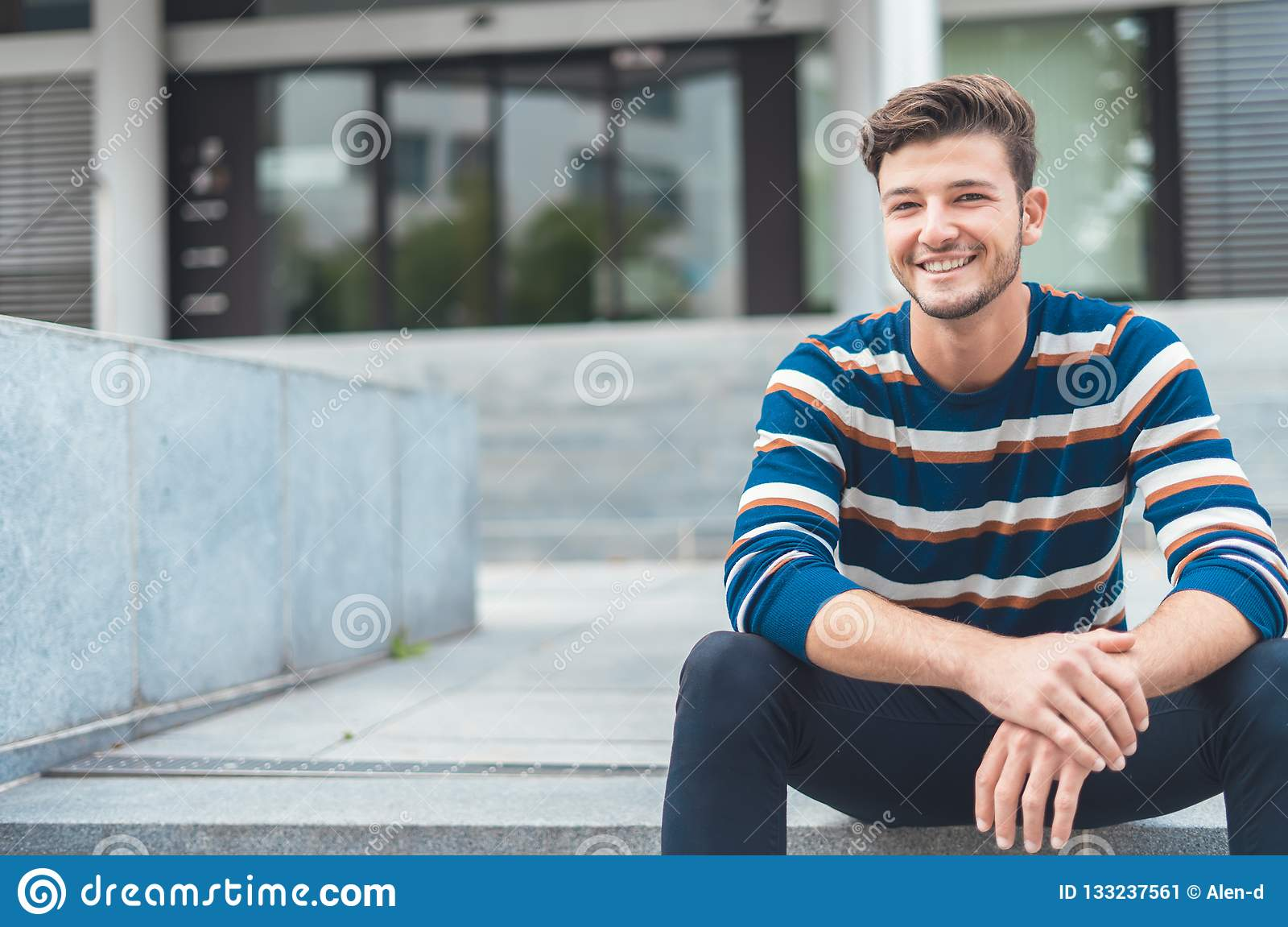 Happy young man sitting in front of entry entrance