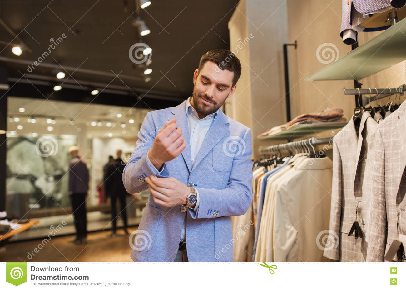be521e34 Sale, shopping, fashion, style and people concept - elegant young man  choosing and trying jacket on in mall or clothing store
