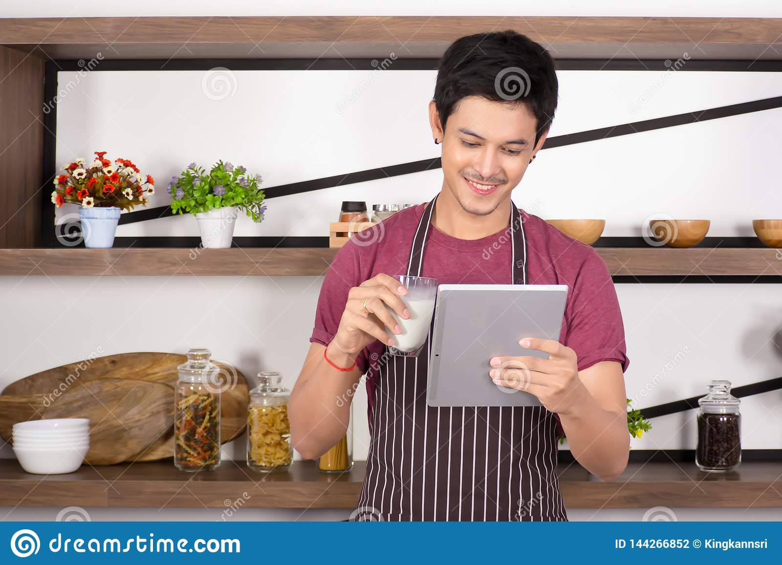 Happy young man wear brown apron holding a glass of milk while using tablet