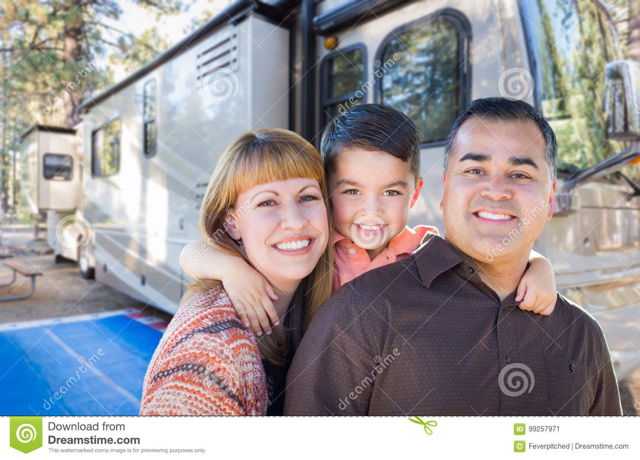 Happy Young Mixed Race Family In Front of Their Beautiful RV At