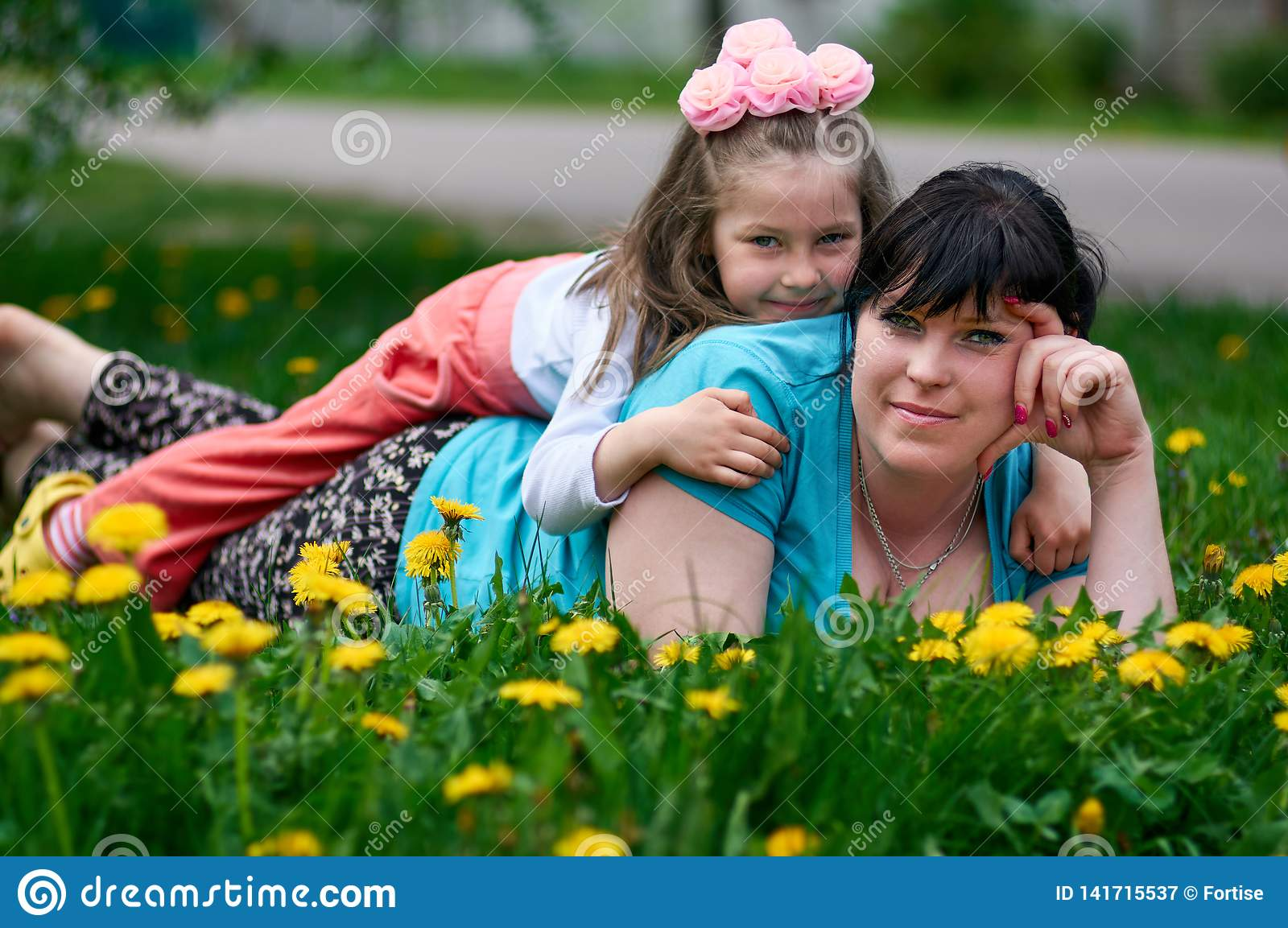 Happy young mother with baby enjoys summer time in a dandelion meadow