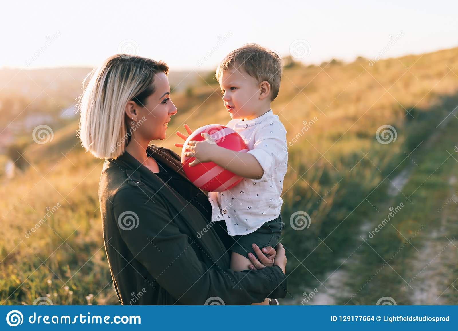 happy young mother carrying adorable little son with red