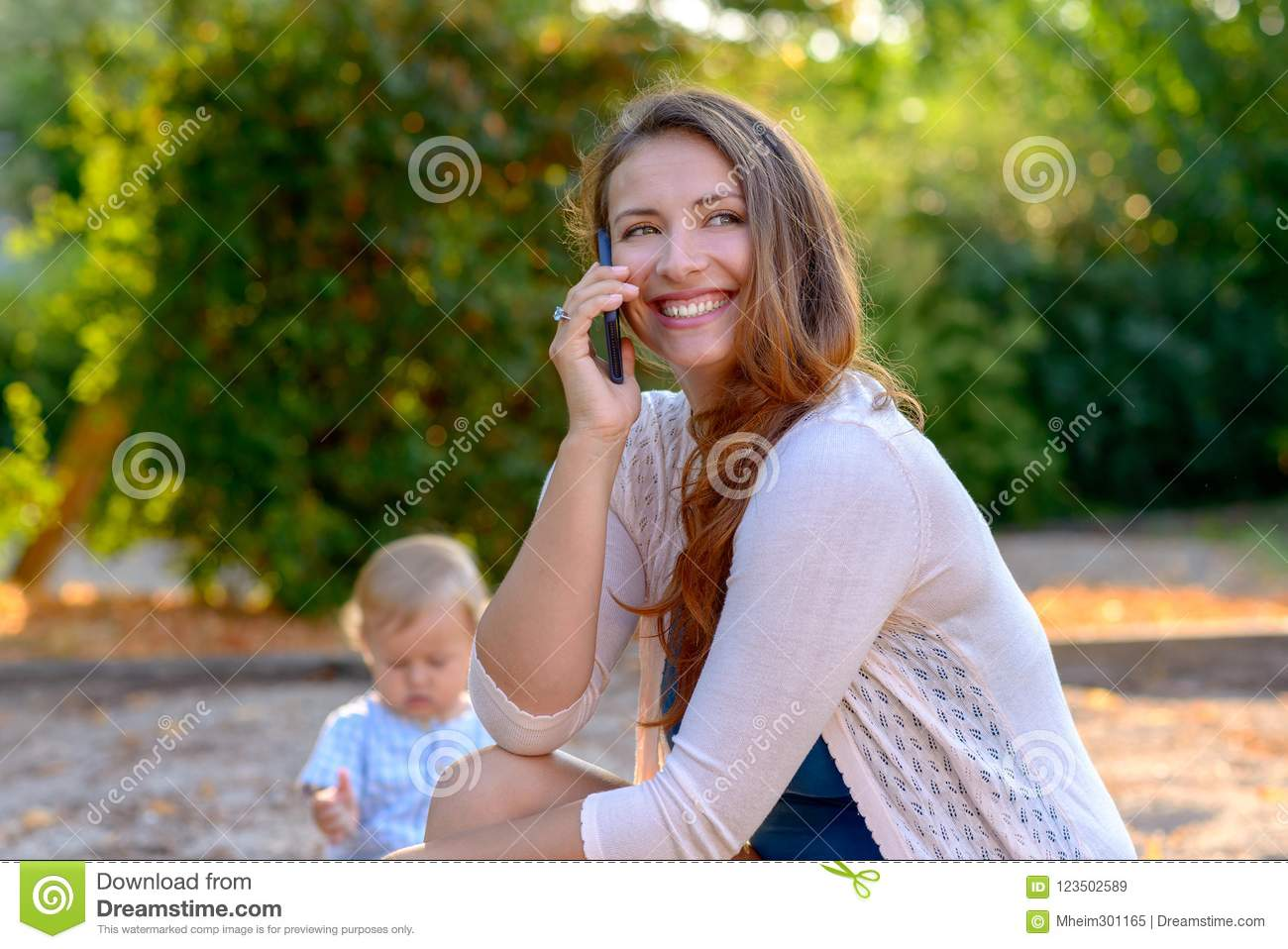 Happy young mother chatting on her mobile