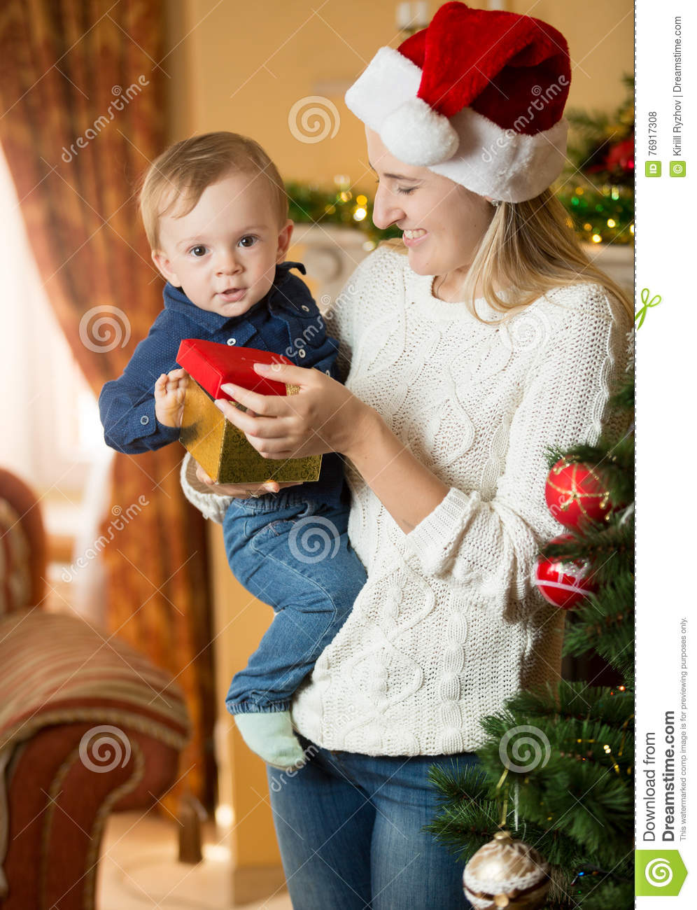 Happy young mother giving gift box to her baby boy at Christmas