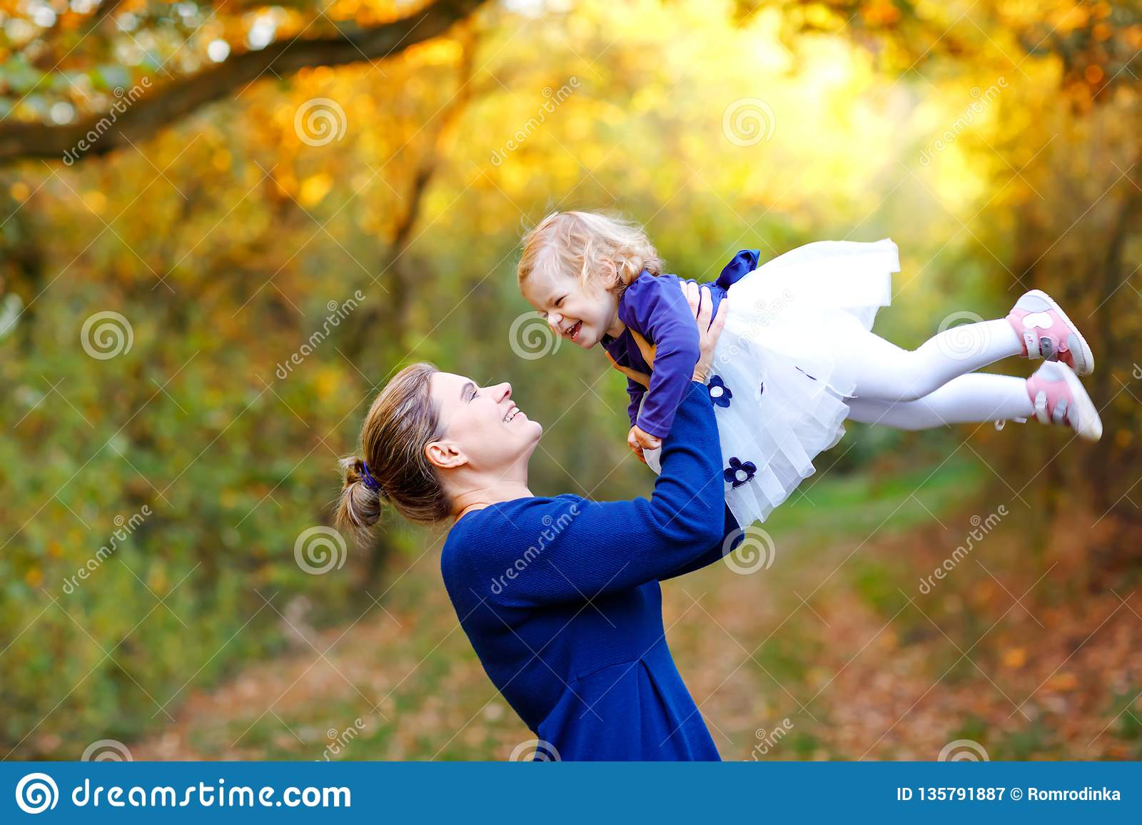 Happy young mother having fun cute toddler daughter, family portrait together. Woman with beautiful baby girl in nature