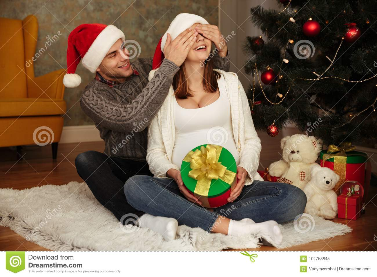happy young pregnant woman with her husband wearing christmas hats