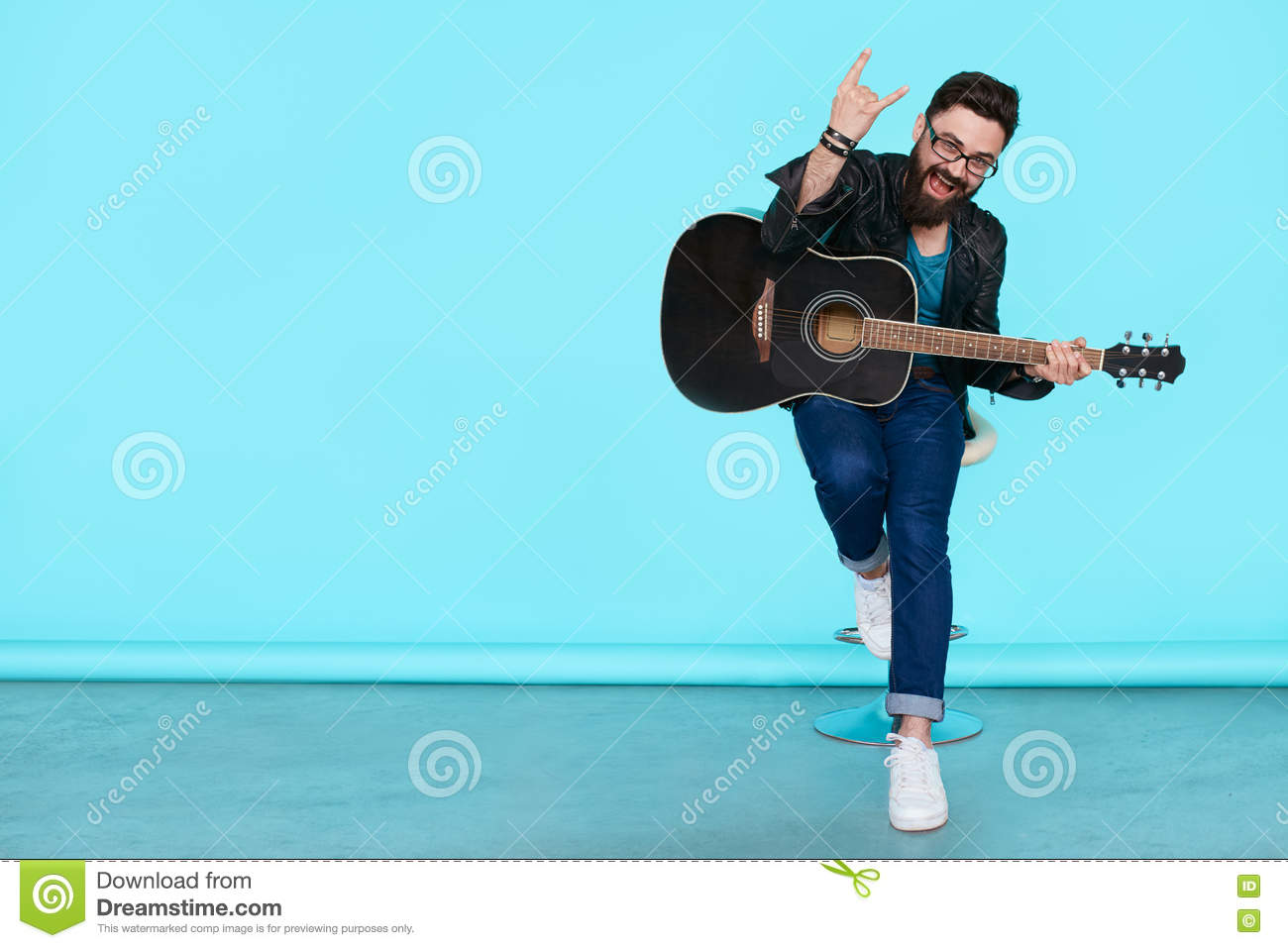 Happy young punk rocker with a guitar and dark sunglasses