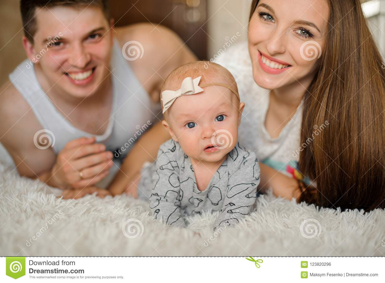 Happy and young smiling parents couple lying on the bed with cute newborn baby girl